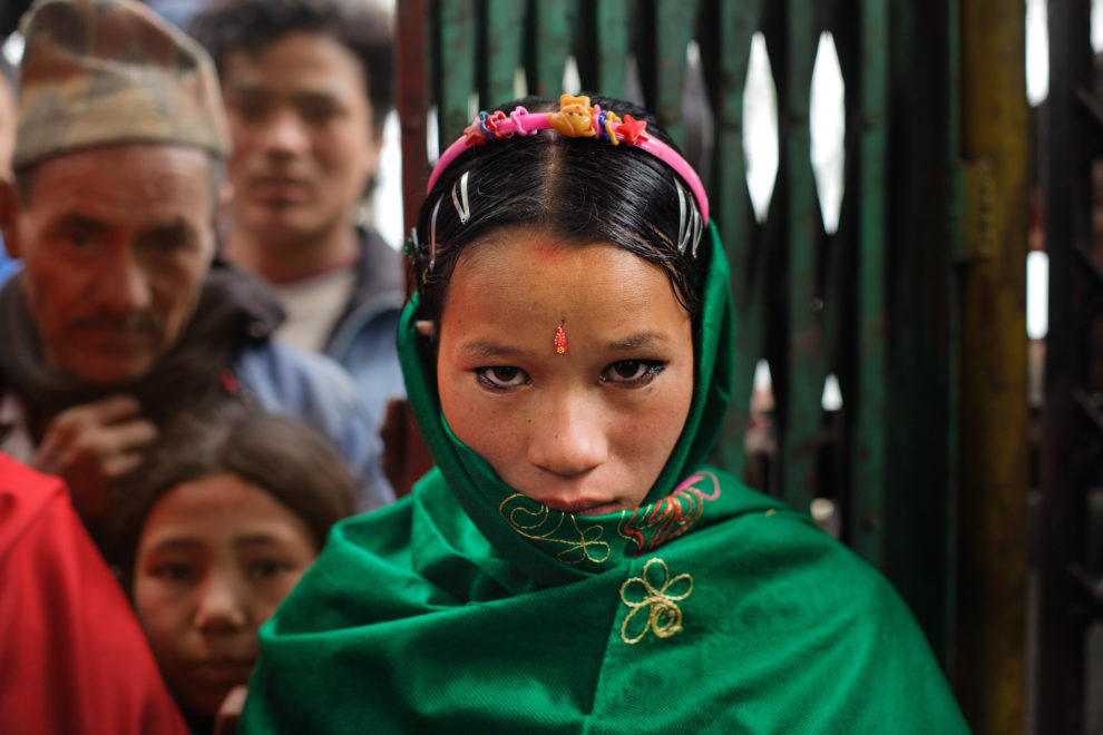 A nine-months pregnant Niruta, 14, arrives at her wedding ceremony in Kagati village Nepal on Jan. 23, 2007, which was the auspicious day of Vasant Panchami, a Hindu holiday celebrating the coming of spring. Niruta moved in with the family of Durga, 16, the year before and was pregnant three months later. The 2015 earthquakes devastated Nepal and left girls and women in an increasingly vulnerable position, leading experts to believe child marriage rates will increase over the coming years.