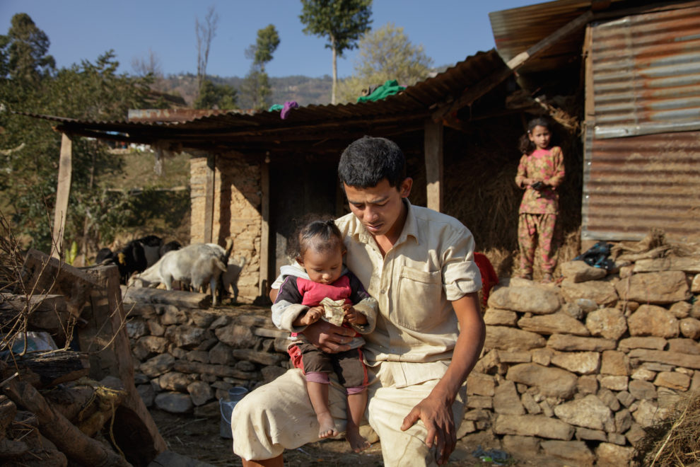 Holding his youngest child, Durga, now 26, sits in frustration in front of the rebuilt shed he shares with Niruta, now 24, their three children, a water buffalo, and a handful of chickens and goats. Niruta and Durga were married 9 years ago, when they were just 14 and 16 years old in the Kagati village of Nepal. The 2015 earthquakes devastated Nepal and left girls and women in an increasingly vulnerable position, leading experts to believe child marriage rates will increase over the coming years.