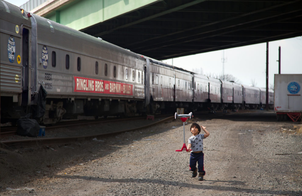 "Kauile dos Santos, 7, the son of Brazilian actor Paulo Cesar Oliveira dos Santos practices his moves near the parked train. He hopes to be just like his father someday. Ringling Bros. and Barnum & Bailey Circus started in 1919 when the circus created by James Anthony Bailey and P. T. Barnum merged with the Ringling Brothers Circus. Currently, the circus maintains two circus train-based shows, the Blue Tour and the Red Tour, as well as the truck-based Gold Tour. Each train is a mile long with roughly 60 cars: 40 passenger cars and 20 freight. Each train presents a different ""edition"" of the show, using a numbering scheme that dates back to circus origins in 1871 — the first year of P.T. Barnum's show."