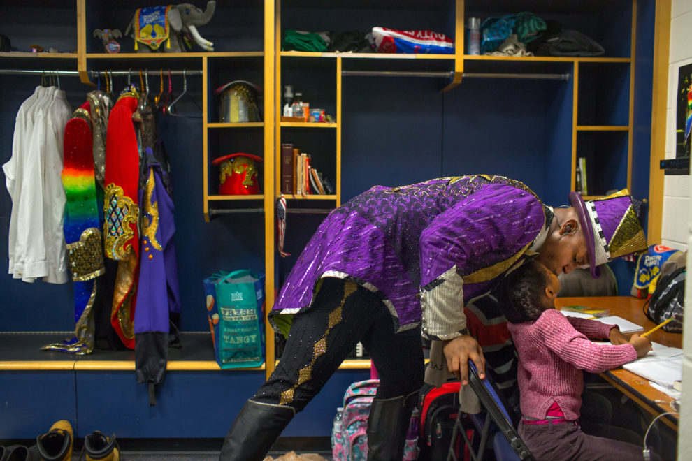 "Ringmaster Johnathan Lee Iverson, 39, gives his daughter Lila, 6, a kiss in his dressing room before a performance. Johnathan Lee Iverson made history at only 22 years old, when he became the youngest, the first New Yorker, and the first African American ringmaster in the nearly 140 year history of Ringling Bros. and Barnum & Bailey circus. Ringling Bros. and Barnum & Bailey Circus started in 1919 when the circus created by James Anthony Bailey and P. T. Barnum merged with the Ringling Brothers Circus. Currently, the circus maintains two circus train-based shows, the Blue Tour and the Red Tour, as well as the truck-based Gold Tour. Each train is a mile long with roughly 60 cars: 40 passenger cars and 20 freight. Each train presents a different ""edition"" of the show, using a numbering scheme that dates back to circus origins in 1871 — the first year of P.T. Barnum's show."